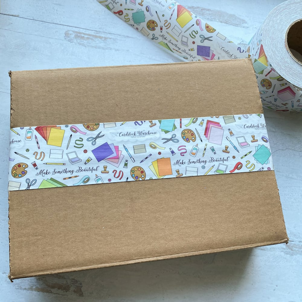 Illustrated packing tape stuck to brown cardboard box with a roll of tape