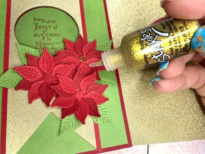 adding gold accents to poinsettia card