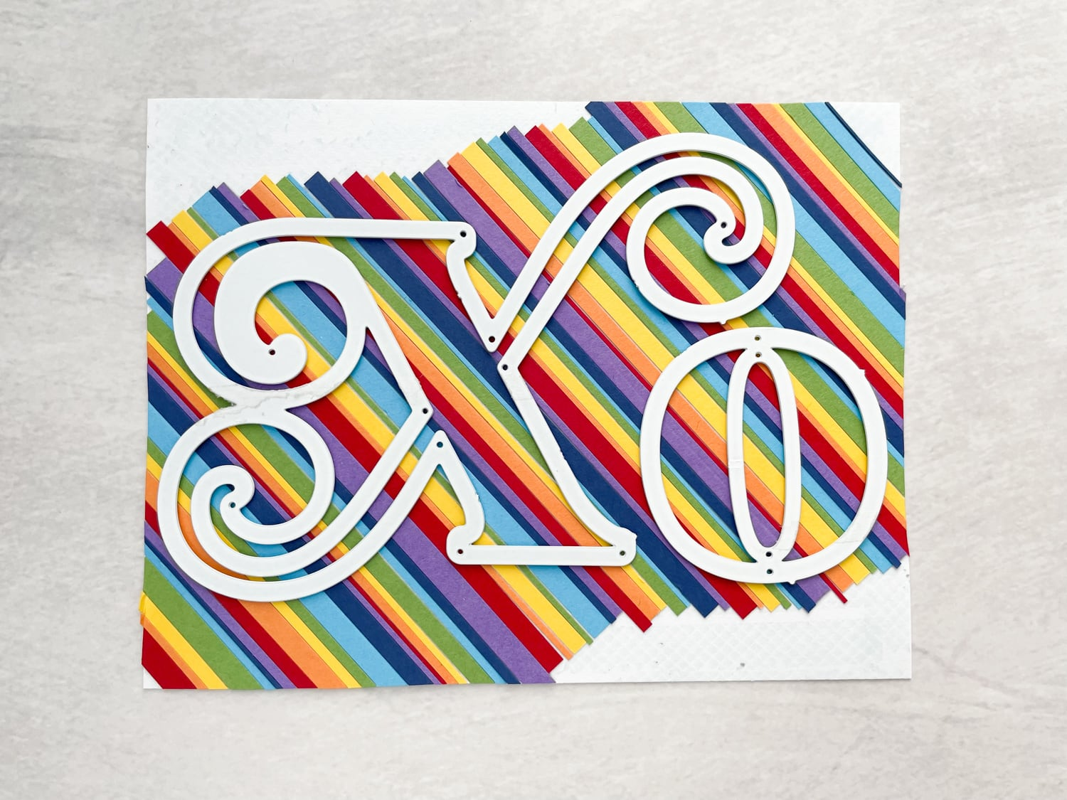 cutting xo out of rainbow paper strips