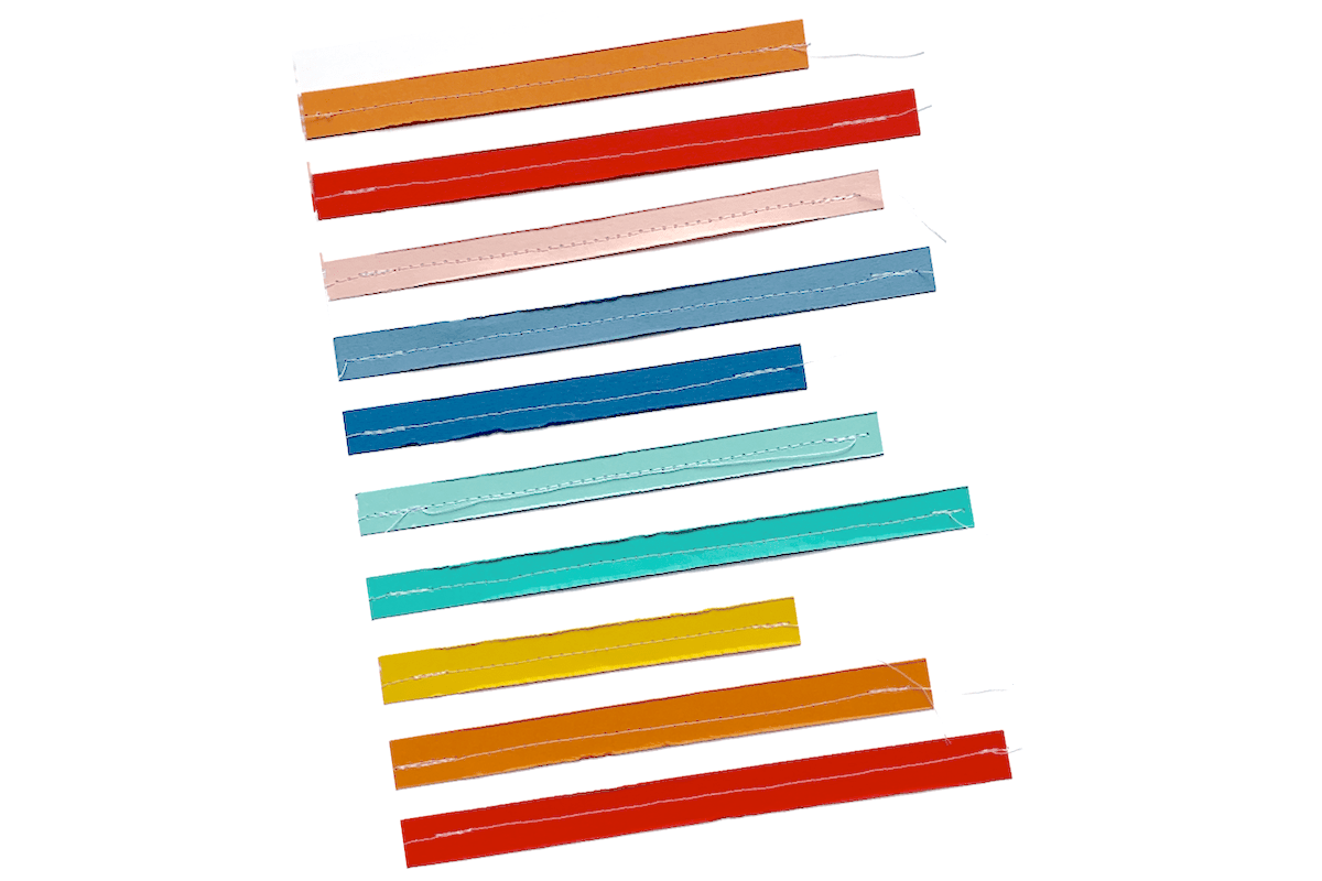 rainbow paper strips stitched onto white paper background
