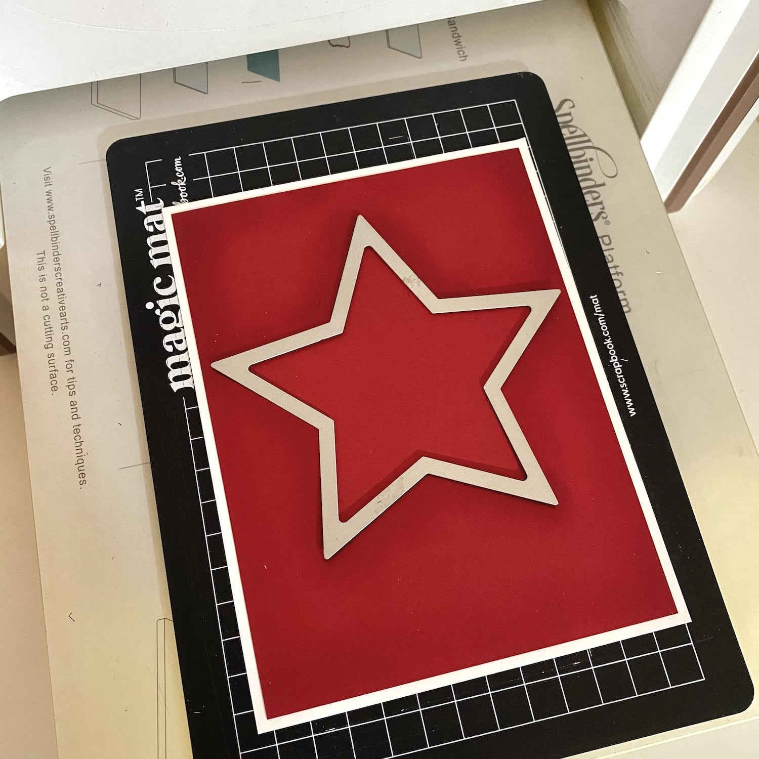 cutting die cut star out of the center of electric red and smart white cardstock layered panel