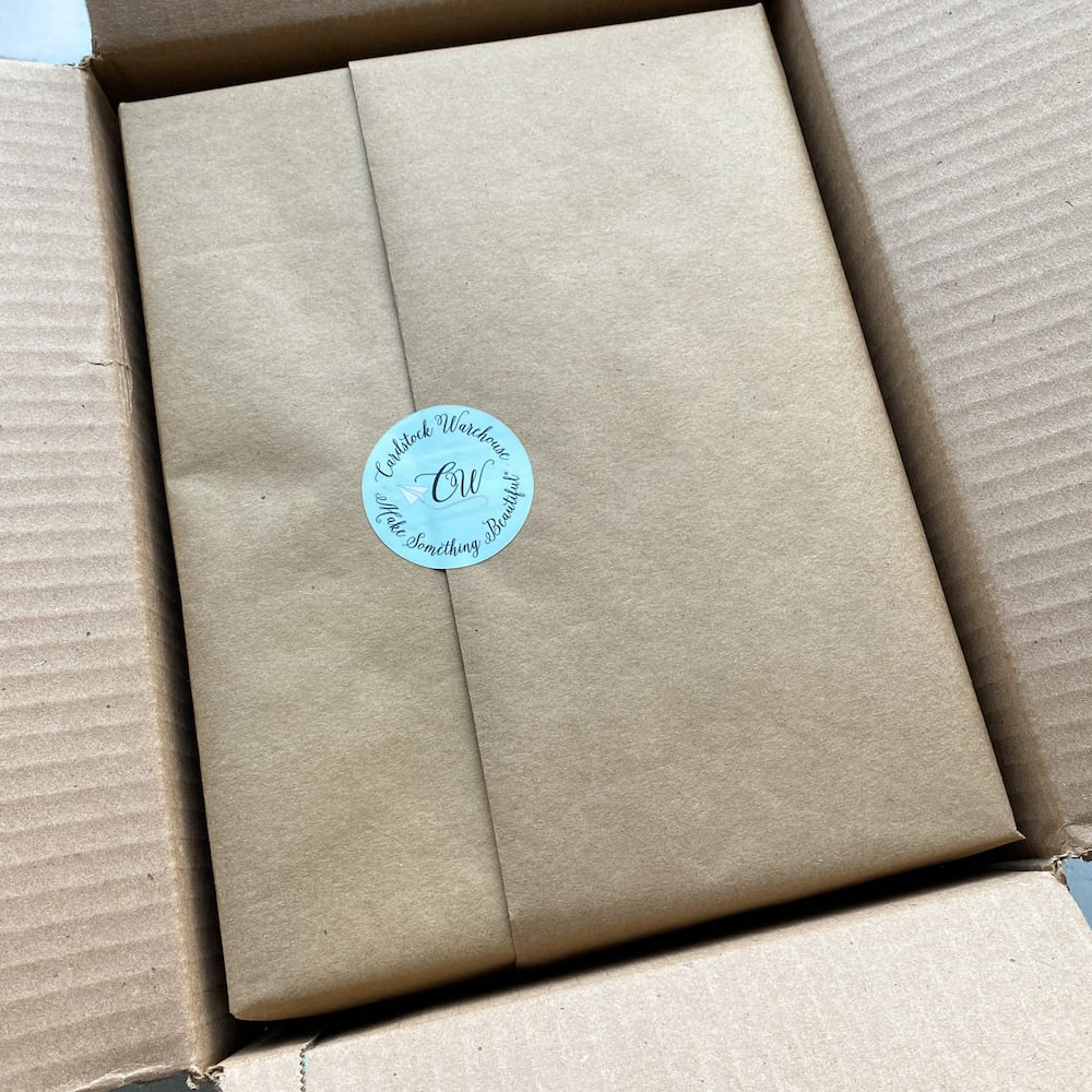 packs of paper wrapped in brown kraft paper with a cardstock warehouse sticker, inside a cardboard box.