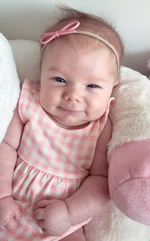 pretty baby girl in pink headband by baby wisp