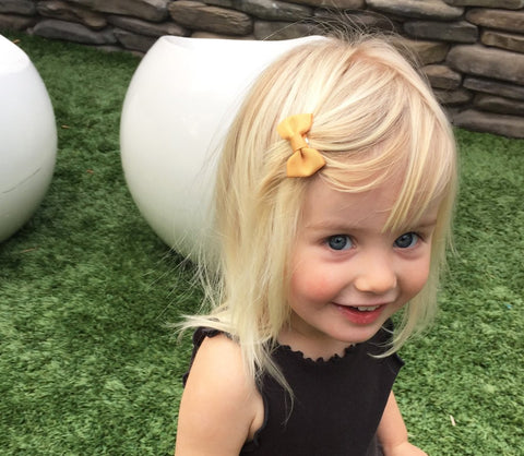 Cute toddler girl wearing Vintage Gold Charlotte Bow by Baby Wisp