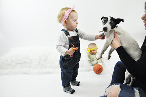 Baby in Topknot Headband during photoshoot playing with Dog