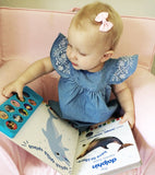 baby girl reading a book with classic baby wisp bow