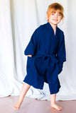 A child wears a navy youth robe.