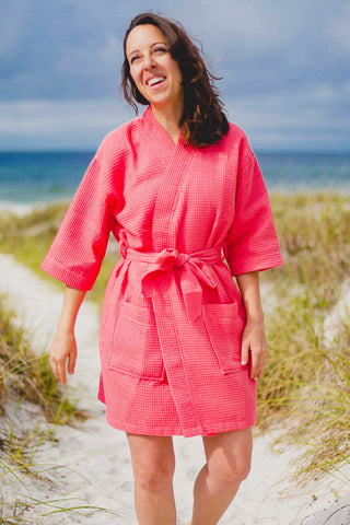 A young woman wears a coral robe on the beach.