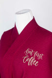 "Detail of wine-colored robe featuring ""But first, coffee"" in latte-colored script text."