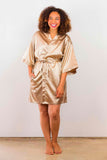 Woman wearing a taupe satin robe.