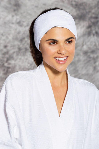 A woman in a white robe wears a white terry cloth headband.