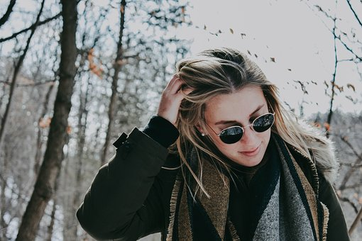 image of girl with sunglasses, long hair with a scarf adnd wool coat outside in the snow