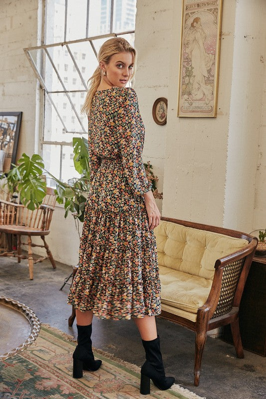 Description Long Sleeve Midi Dress V-Neck Surplice with Hidden Snap Closure Smocked Waist Band Elastic Bands at Wrist All Over Floral Print Tiered Ruffled Skirt Lined Below the Waist