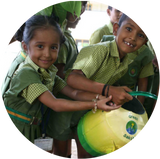 Photo of children watering a plant