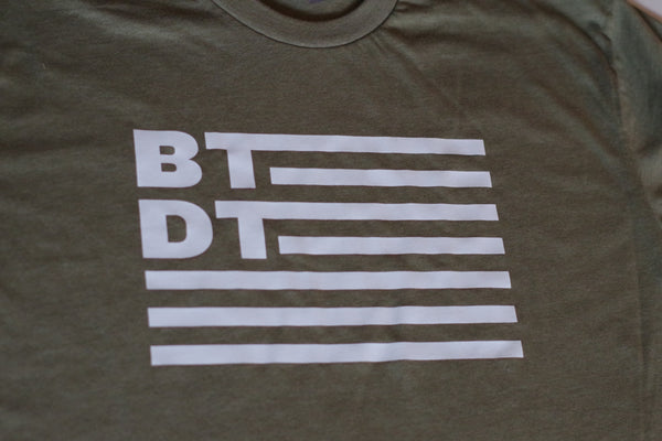 Our classic T-shirt with flag logo. Olive green shirt with white ink