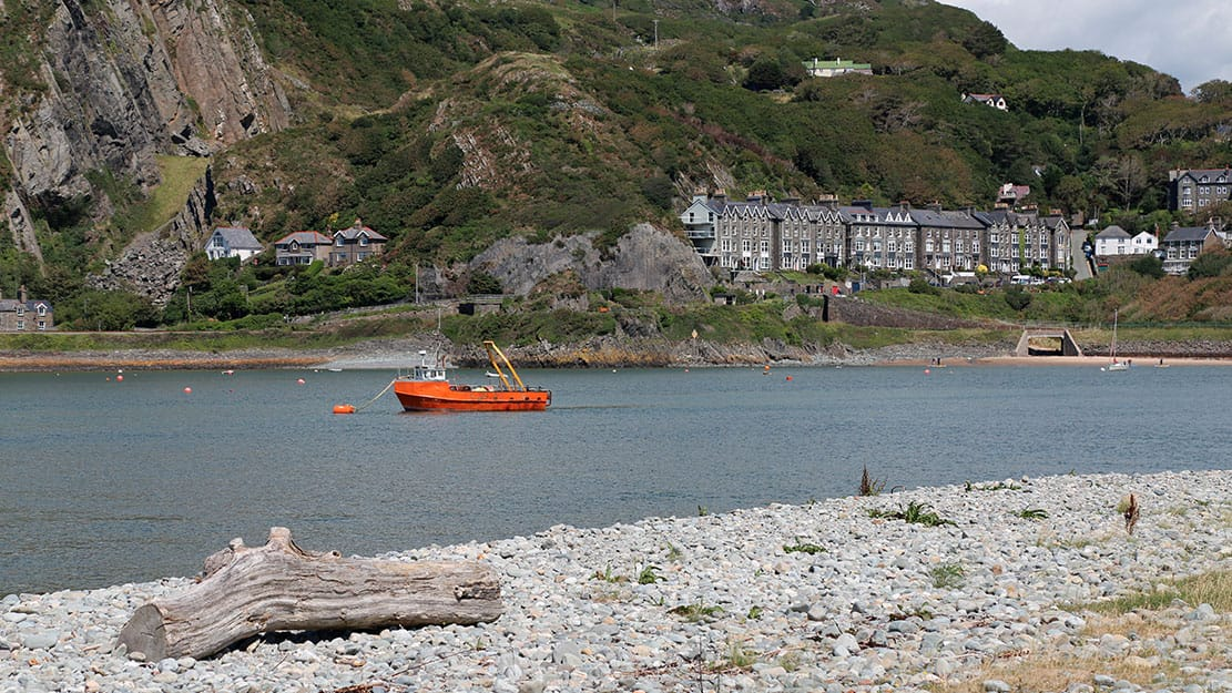An orange fishing boat moored in the Mawddach Estuary with Wales in the background
