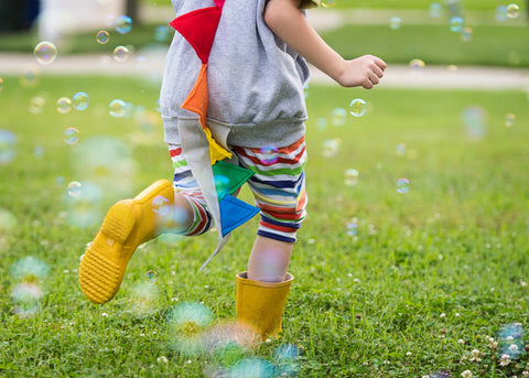 kid with rainbow dinosur tail running in bubbles with rubber boots