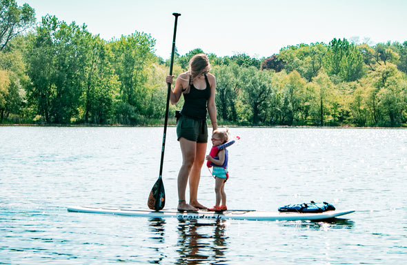 Mother & Daughter standing on a Grey Duck Paddle Board