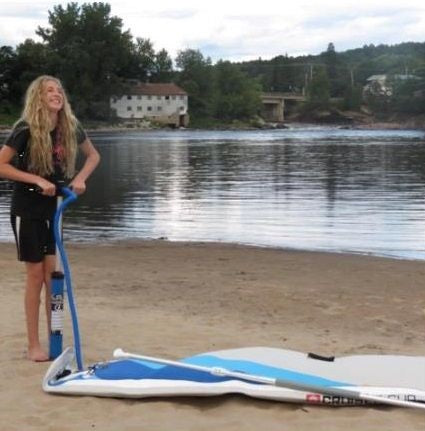 A small female struggling to inflate an inflatable stand up paddle board