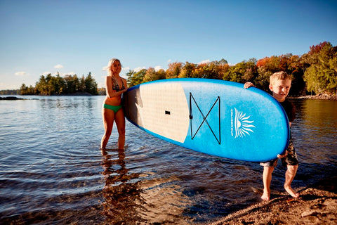 Mother and Son Carrying a Stand Up Paddle Board