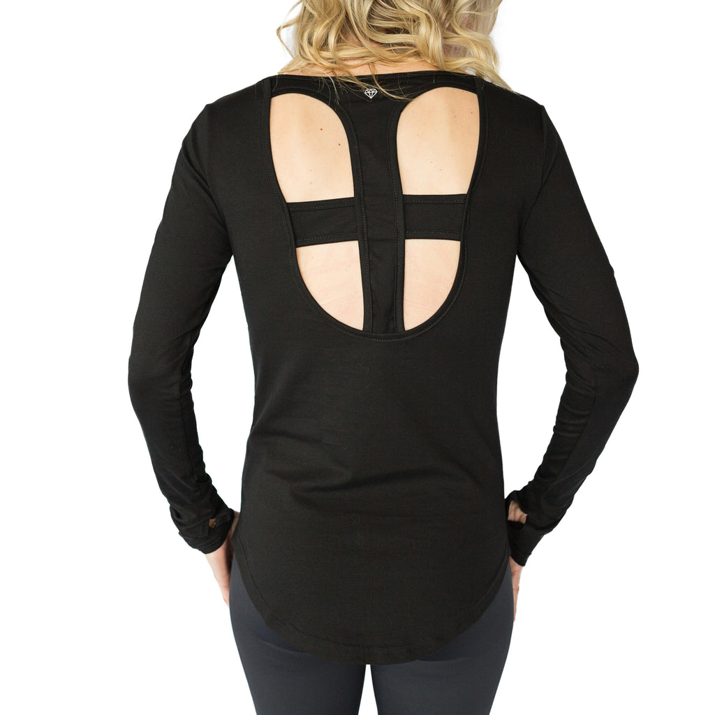 Fit For Barre Open Cross Back Top in a bamboo blend black fabric, with thumbhole sleeves and a longer, rounded hem in the back.