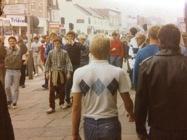 man walking down the street in an 80s argyle jumper with a diamond pattern