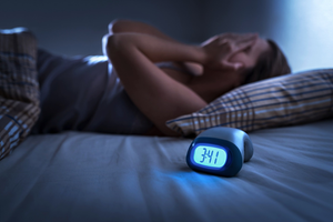 clock reads 3:41 AM woman laying awake
