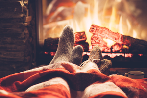 Couples feet in front of cozy fireplace