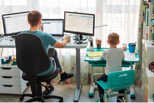 Father and son working at desks side by side