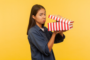 Woman with sad face opening present