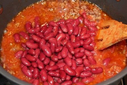 Adding the crushed tomatoes and red beans