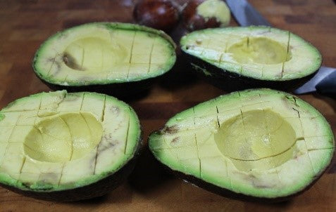 Cut avocados in half and remove the pit.