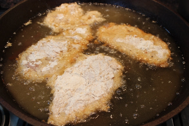 Chicken just placed into the frying oil, before being turned.