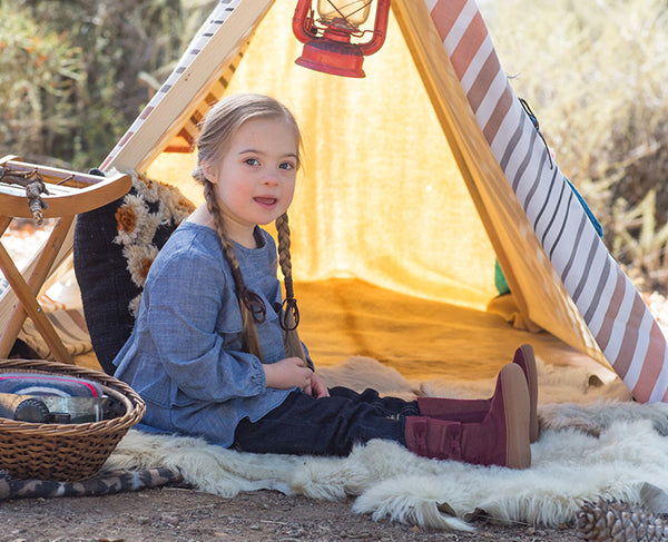 Little girl with Down Syndrome wearing boots by a tent