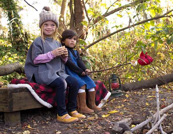 Two little girls by the campfire, one with down syndrome