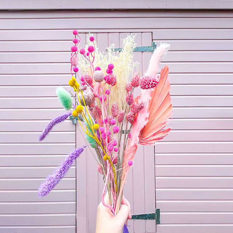 A Happy Bunch - Sherbet Rainbow Dried Flowers | Baked Blooms Hands holding in front of pink shed