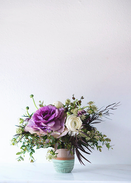 white rununculs, purple cabbage, and various greens make up this whimsical floral arrangement