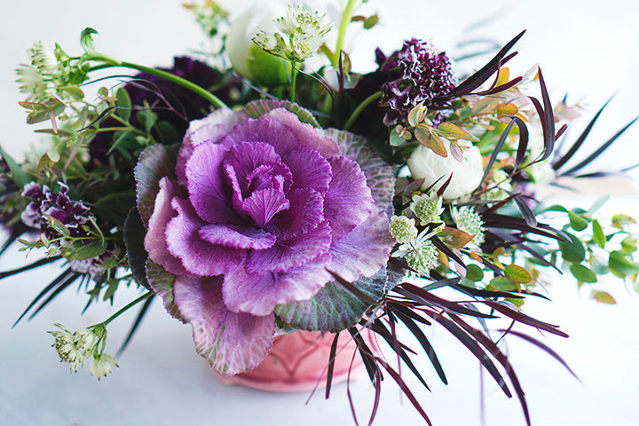 a romantic purple and white floral arrangement featuring a bold cabbage for a statement-making style