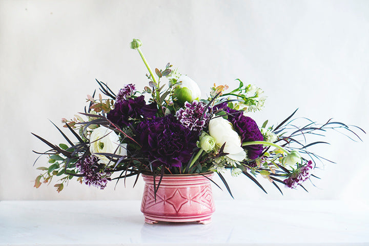 a whimsical purple and white floral arrangement in an art deco antique pink vase