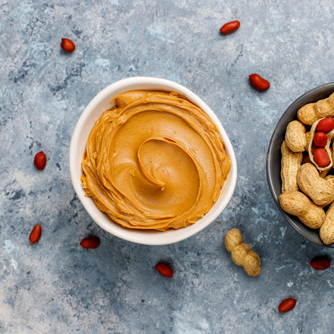 homemade-peanut-butter-with-peanuts-grey-concrete-table-top-view