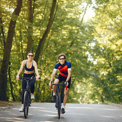 sports-couple-riding-bikes-summer-forest