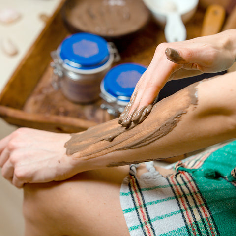 woman-hamam-applying-brown-mud-mask-her-arms