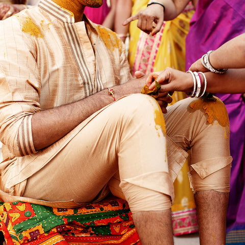 woman-paints-indian-groom-s-knees-face-with-turmeric-paste