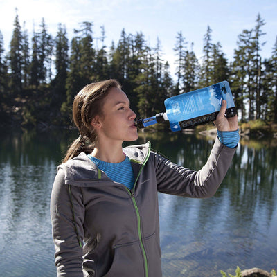 woman drinking from sawyer filter in front of lake