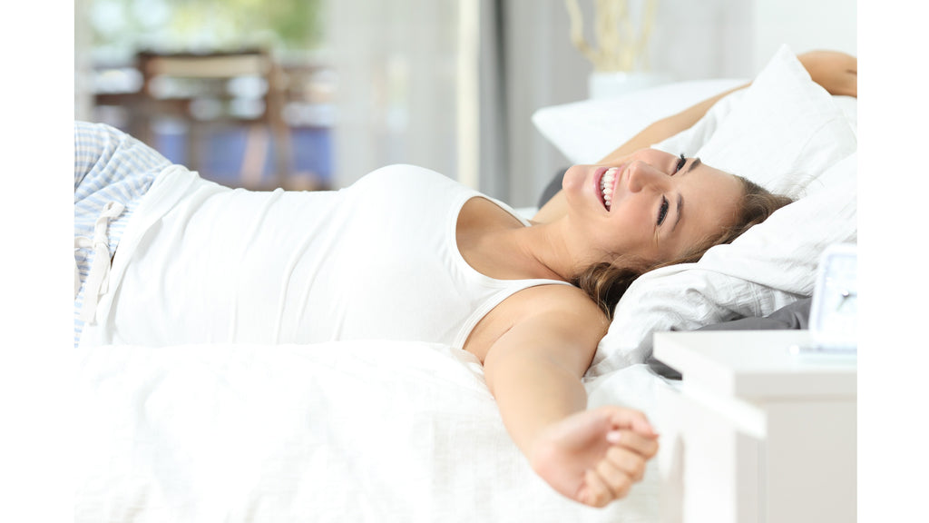 Happy lady waking up in comfortable bed