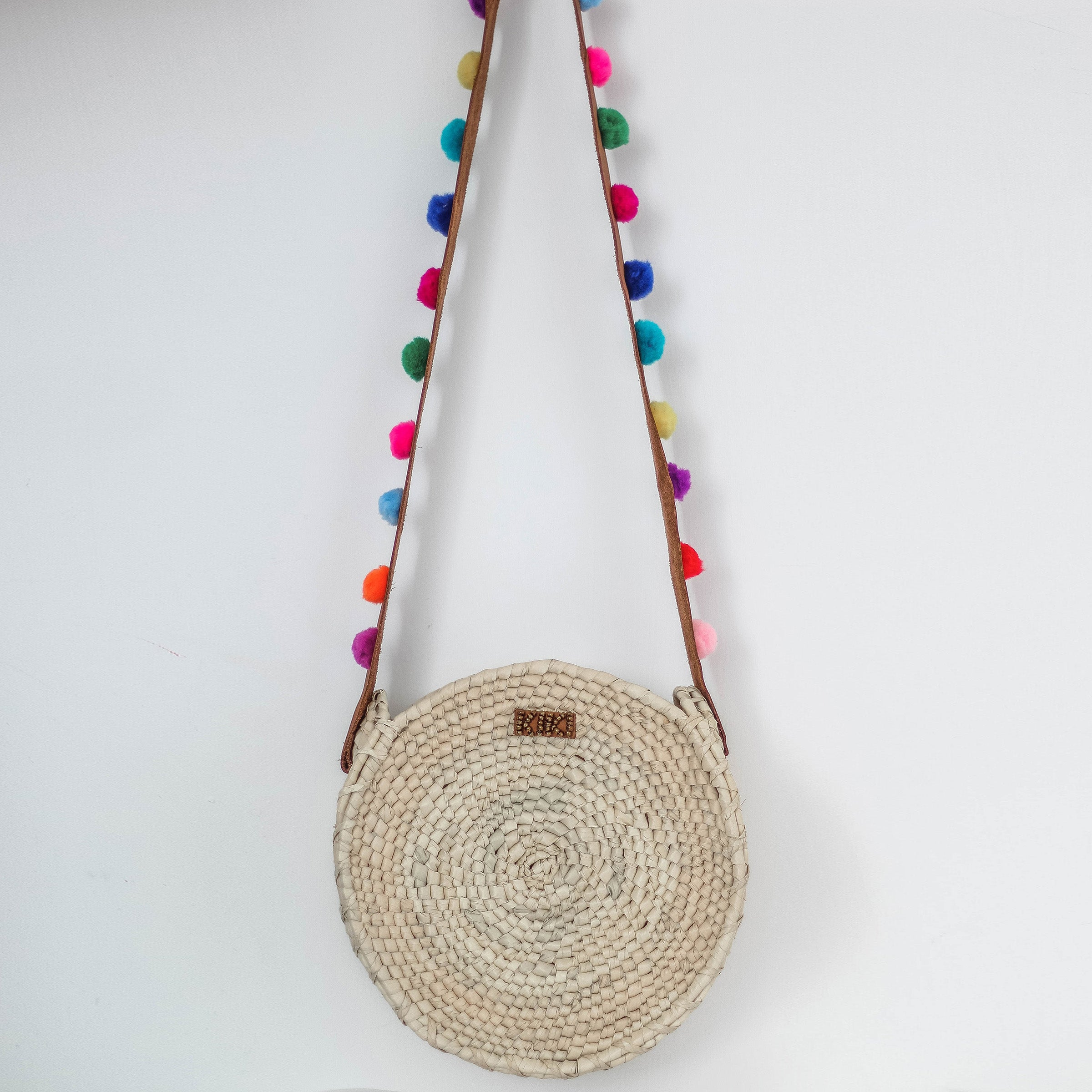 Handmade bag of palm with leather handles and colorful pom poms. 414f65fe8