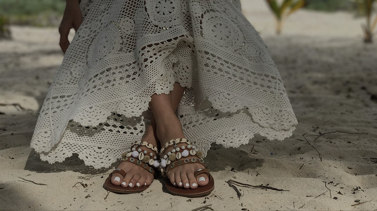 Leather sandals decorated with seashells and pom poms