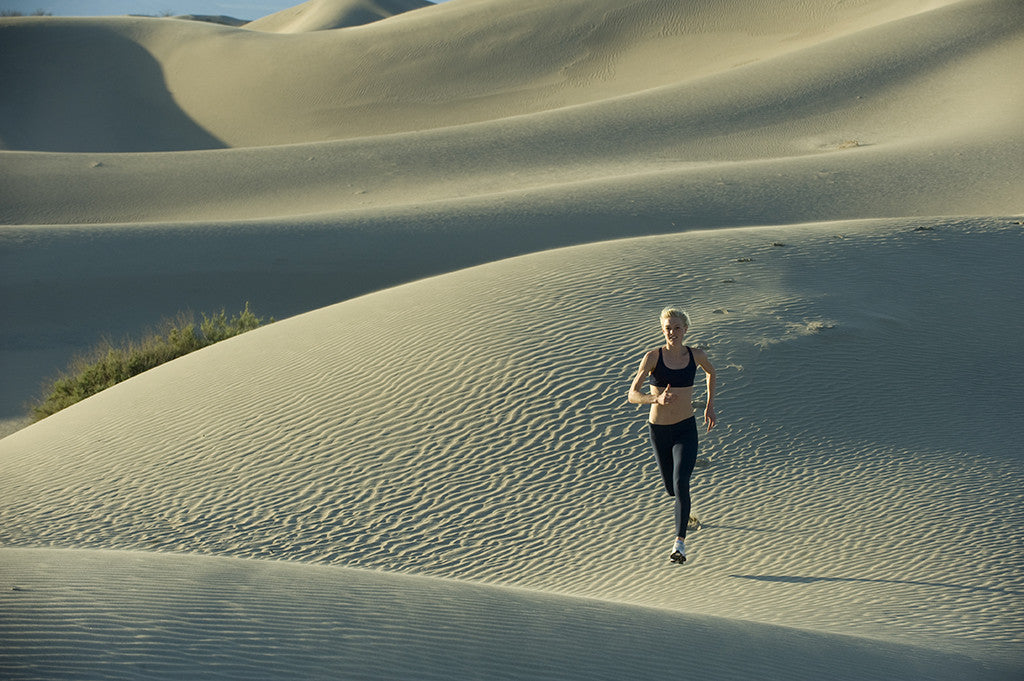 Female runner running across dunes in the desert