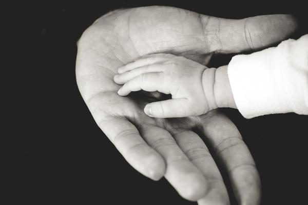 A black and white photos of a child's hand placed in an adults hand.