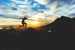 Man jumping in the mountains with the sun setting in the distance